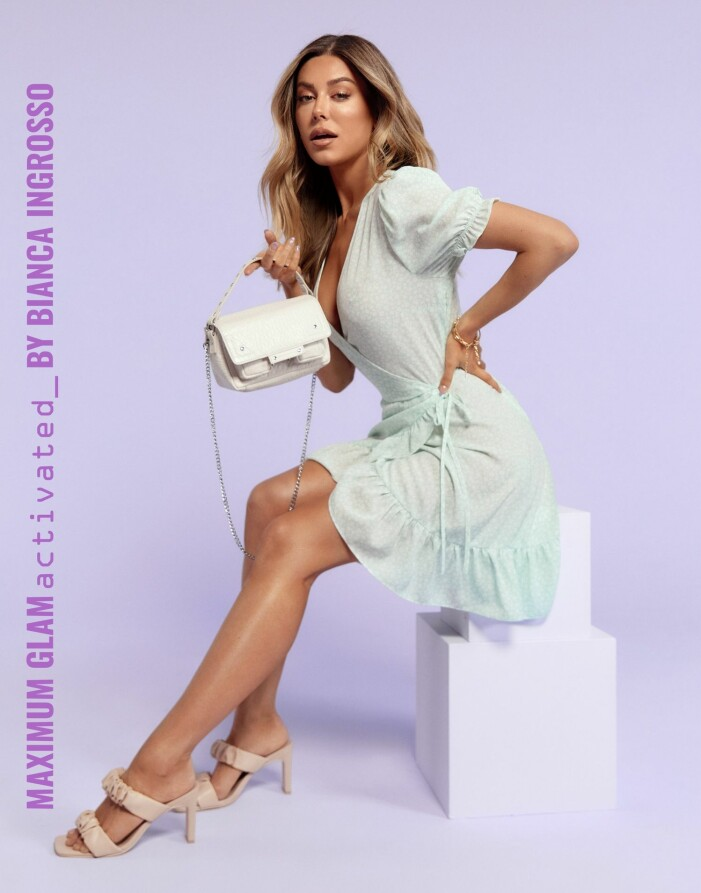 Bianca Ingrosso i en somrig omlottklänning med volanger, beiga klackar och en vit väska från Nelly.