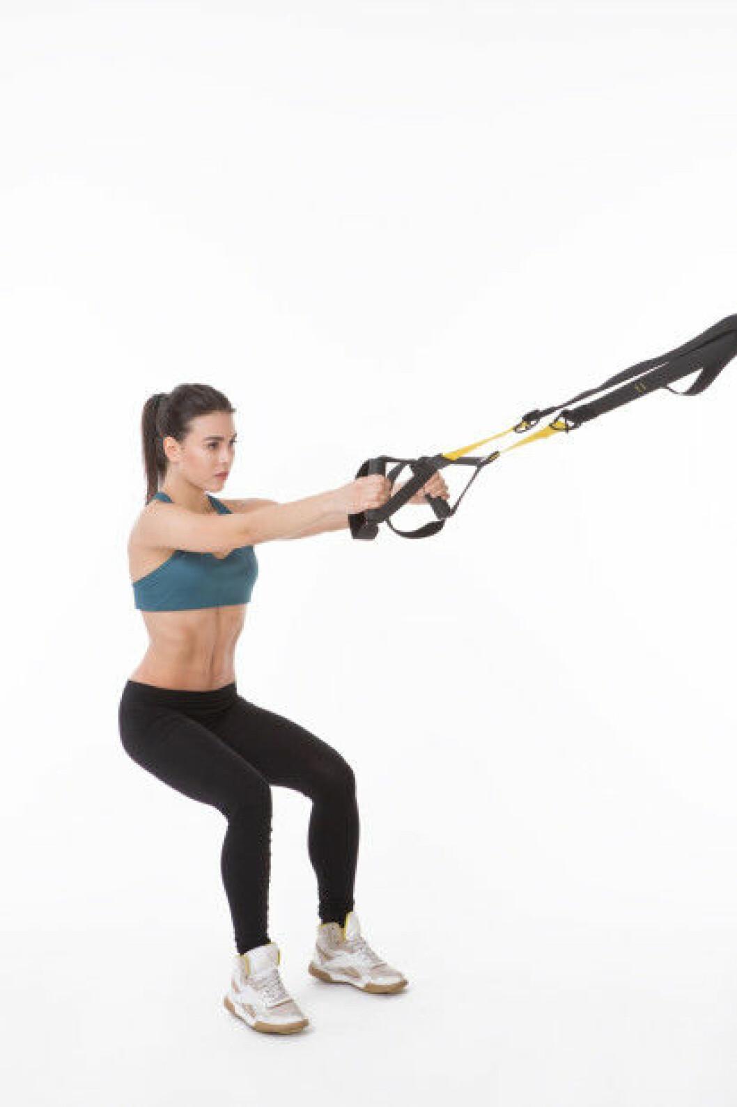 Gör squat med hjälp av TRX banden.