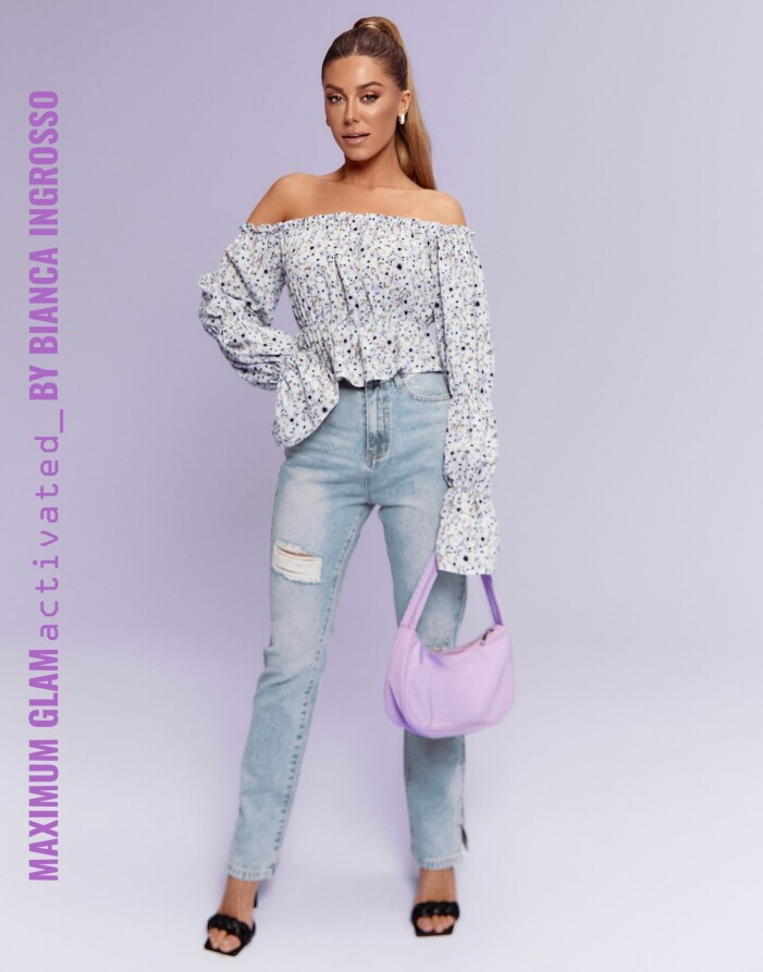 Bianca i en vårig outfit med blommig singoallatopp, ljusa jeans och svarta flätade klackar.