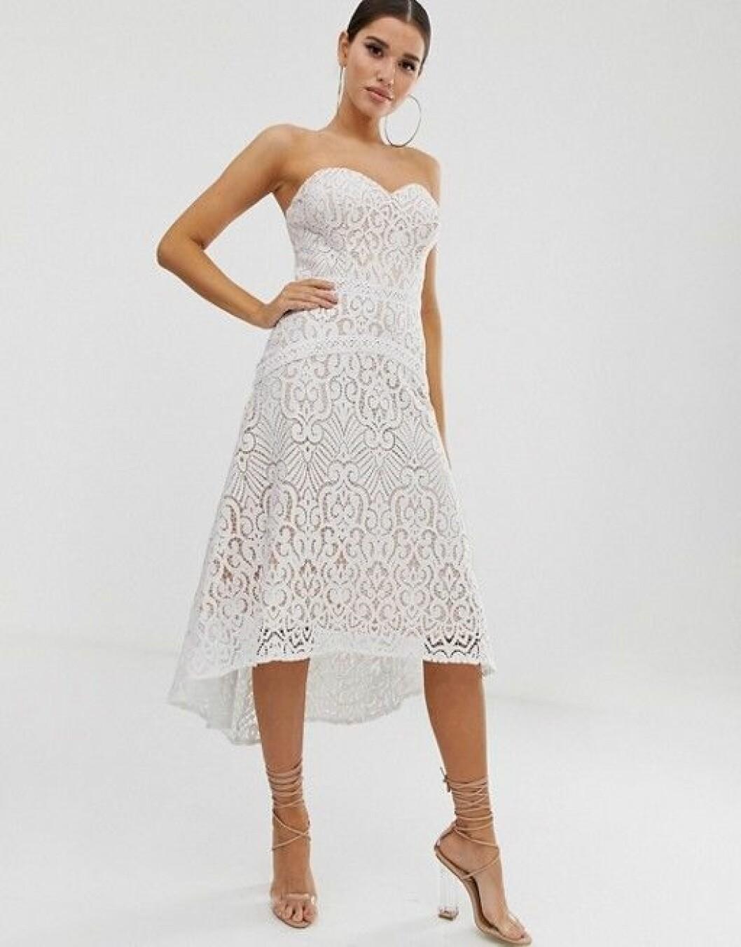 En bild på en vit klänning i spets med hjärtringning från Lipsy.