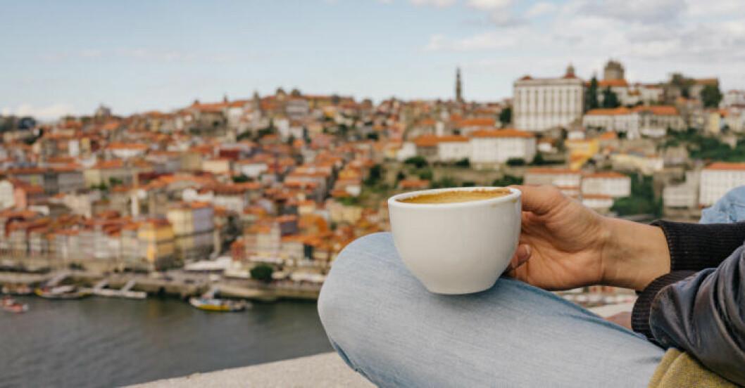 Bild på en kaffekopp med staden Porto i bakgrunden
