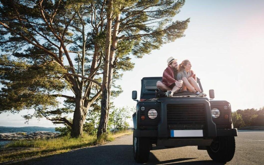 Man och kvinna sitter på motorhuv.