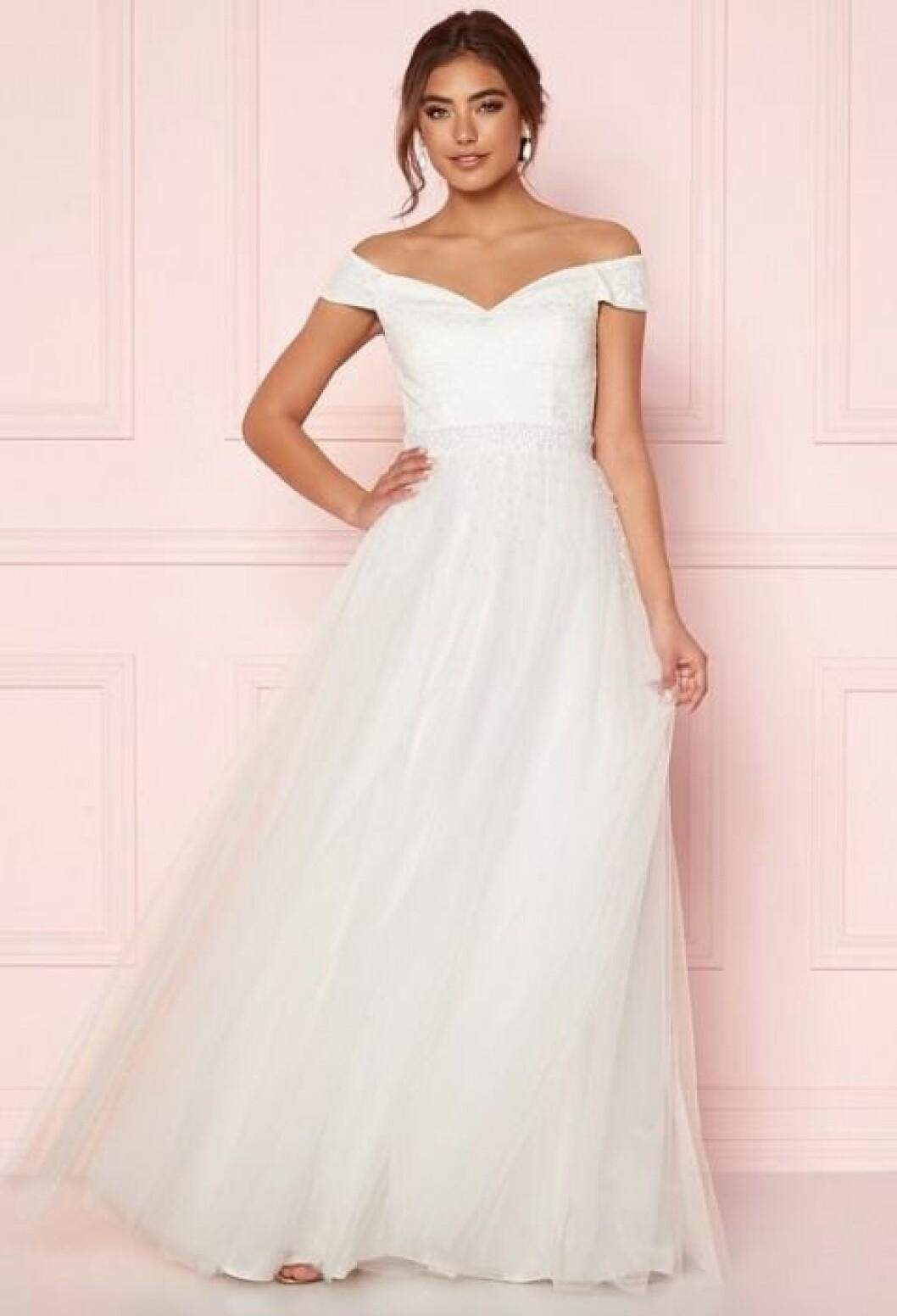 En bild på en brudklänning i tyll med spets- och pärldetaljer från Bubbleroom.