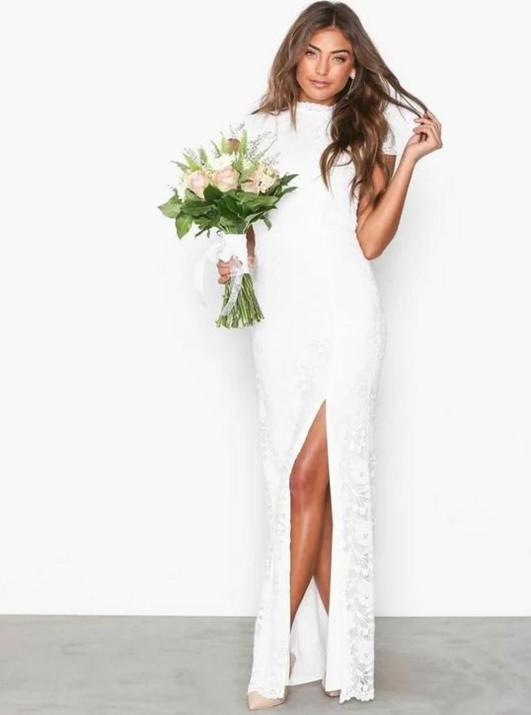 En bild på en brudklänning i spets med öppen rygg och hög slits från Nelly.