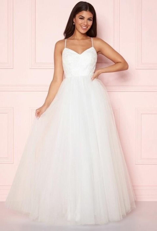 En bild på en brudklänning i tyll med spetsdetaljer och tunna axelband från Bubbleroom.