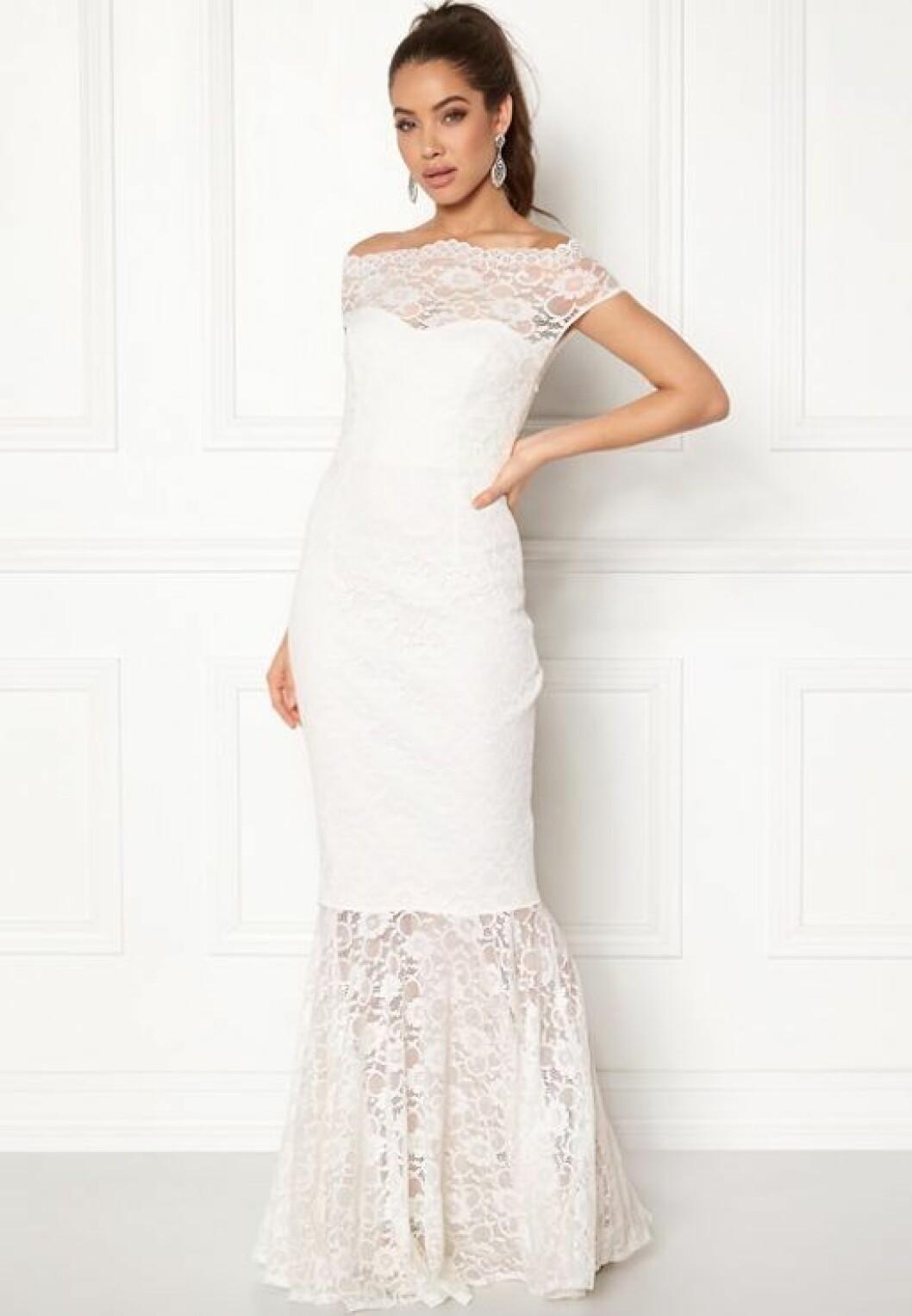 En bild på en vit klänning i fishtailmodell med spetsdetaljer från Goddiva.
