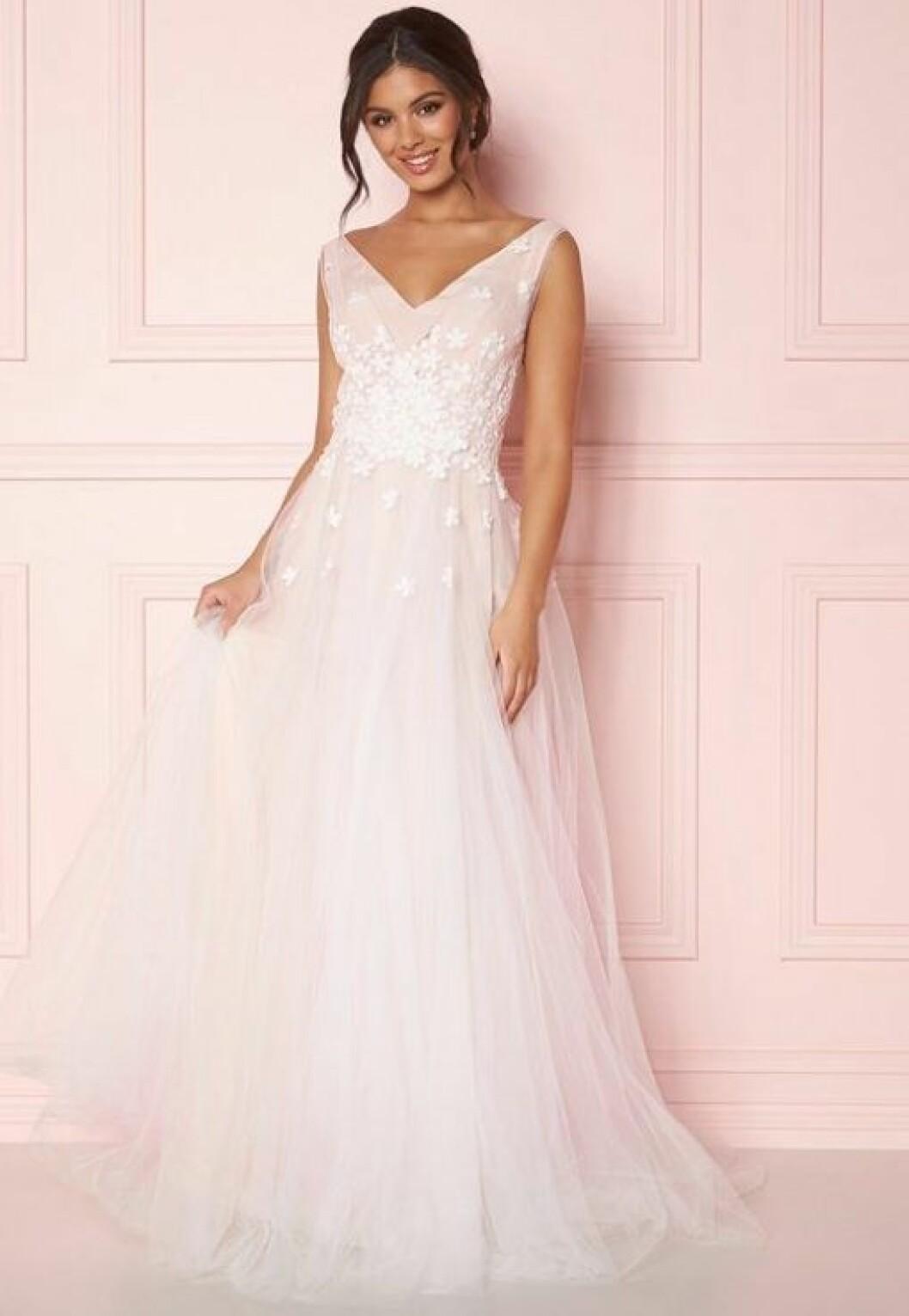 En bild på en brudklänning med detaljer i handgjord spets och djupt ringad rygg från Zetterberg Couture.