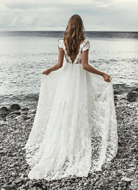 En bild på en bröllopsklänning i tyll med handgjorda blomdetaljer från By Malina.
