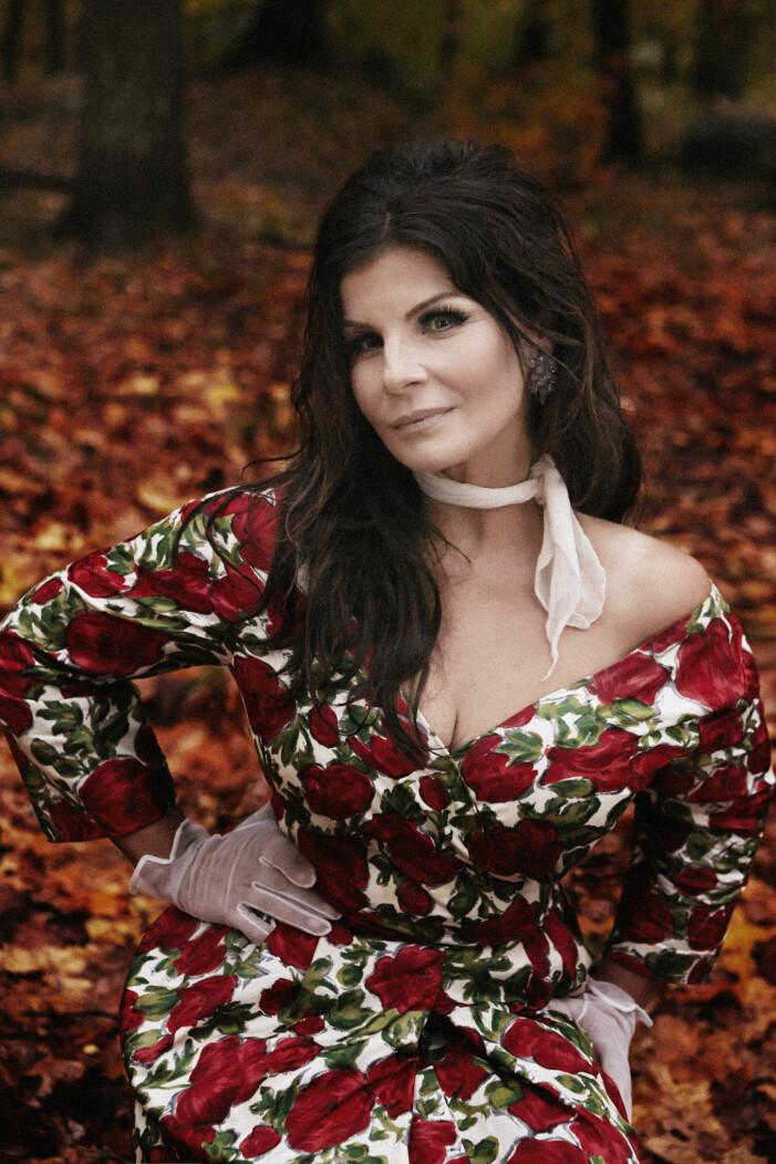 Carola i rödblommig klänning bland höstlöv