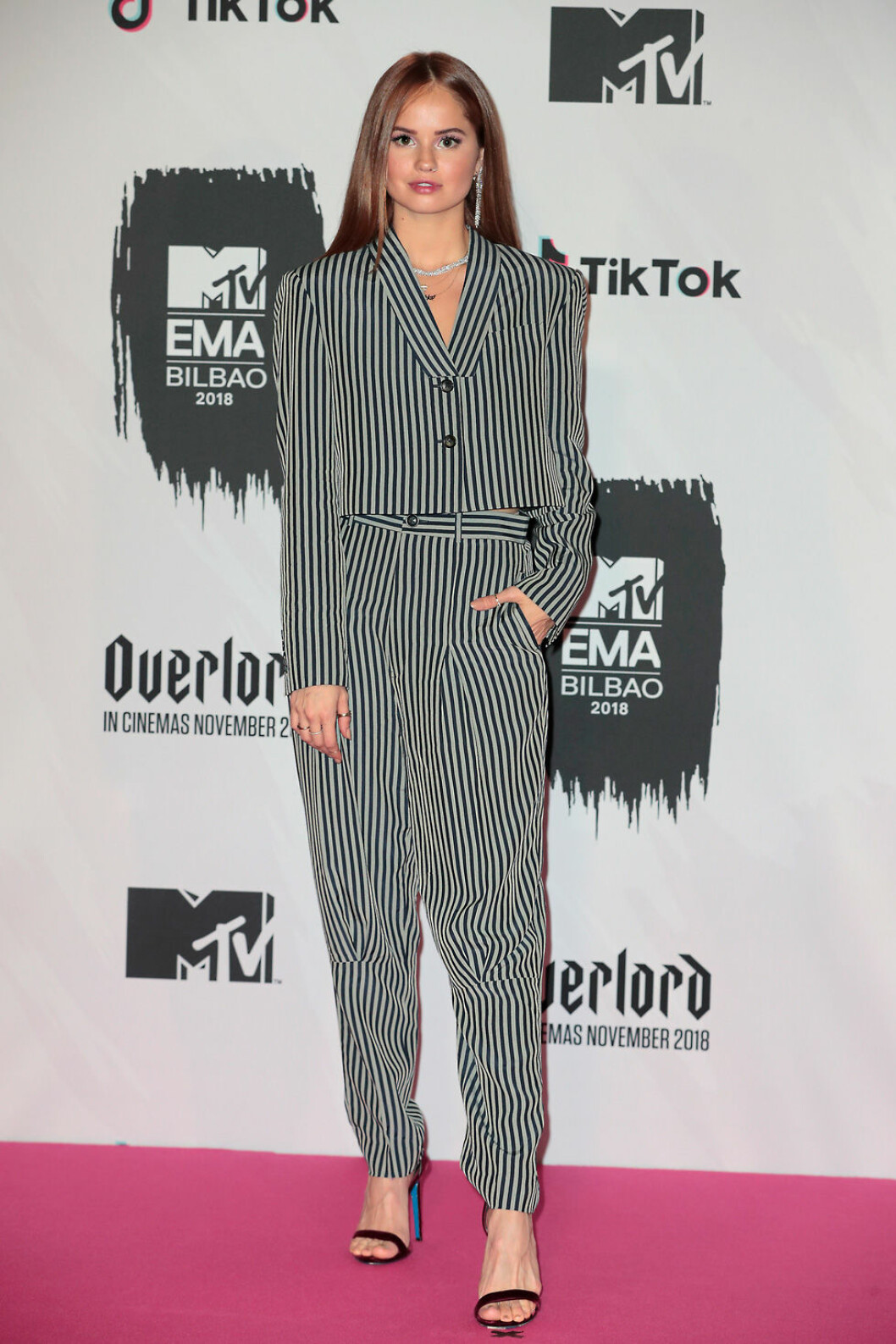 Debby Ryan i randig kostym på röda mattan under MTV EMA 2018.