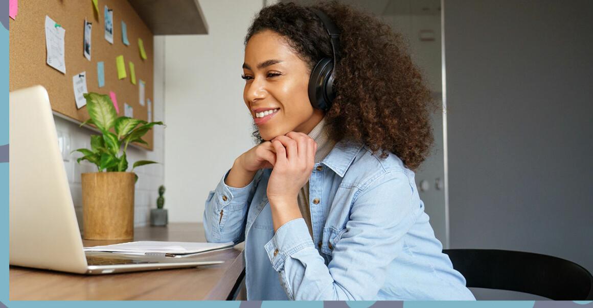 Kvinna ler framför datorn