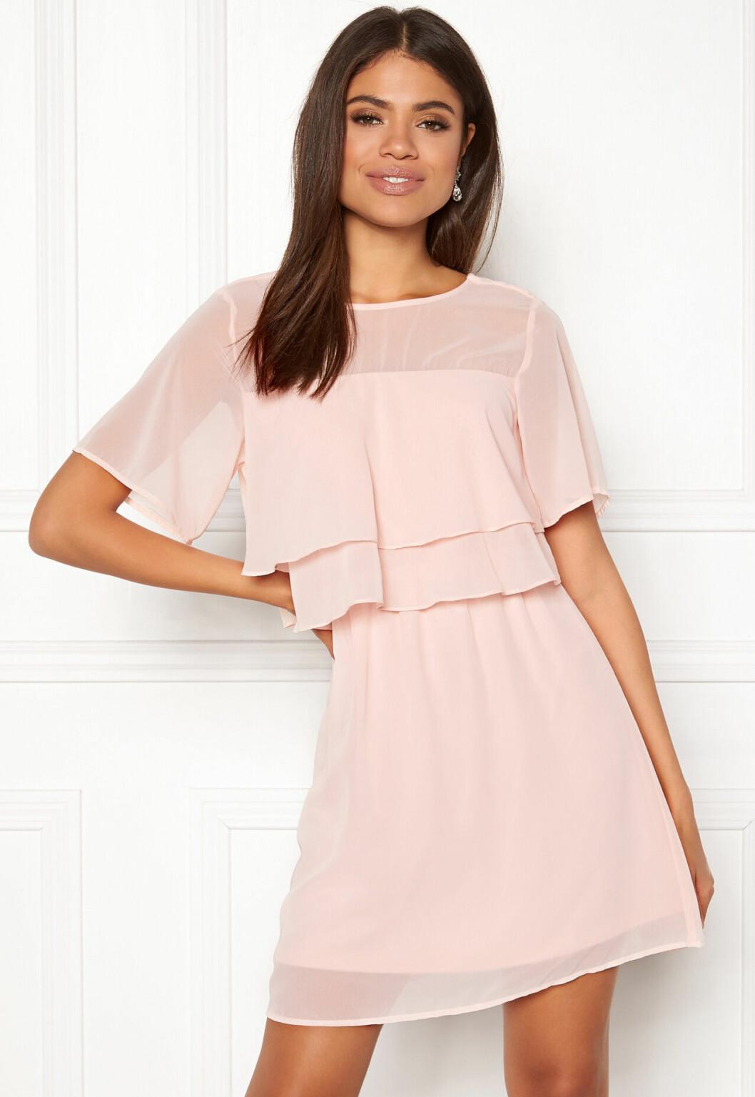 En bild på en pastellrosa klänning med volangdetaljer från Vero Moda.