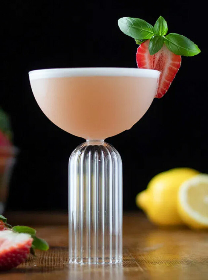 skummig drink i högt glas med jordgubb och basilika