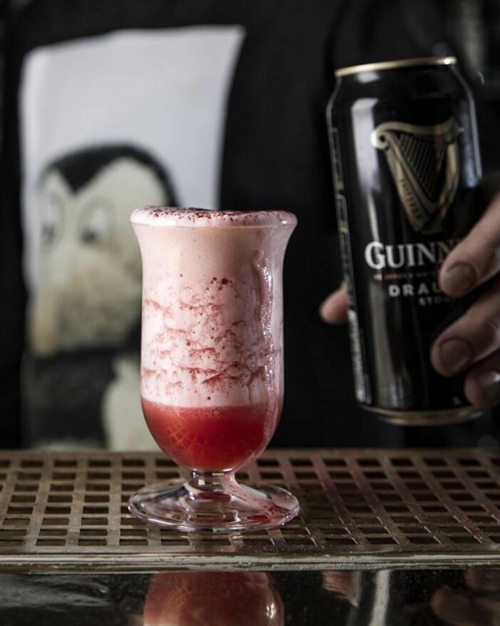 Rosa drink med skum, och en burk Guinness
