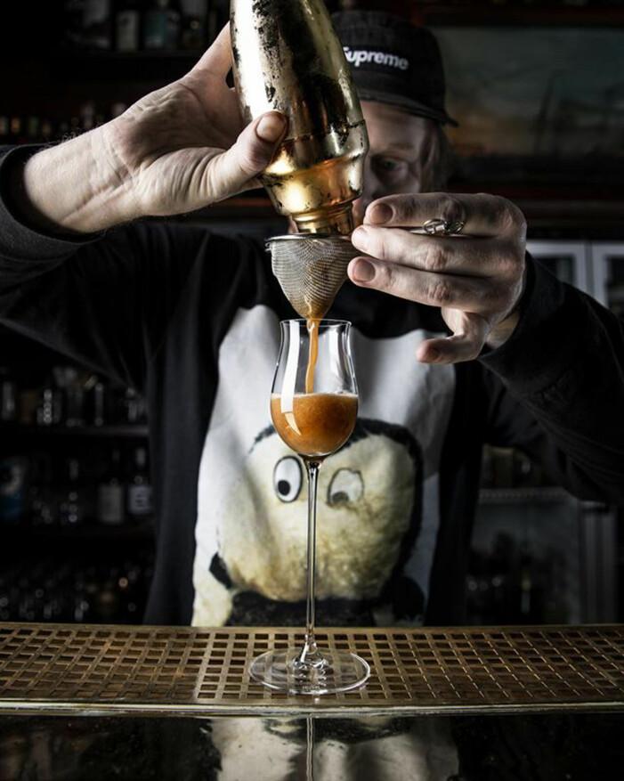 Man häller upp en brun drink i ett glas