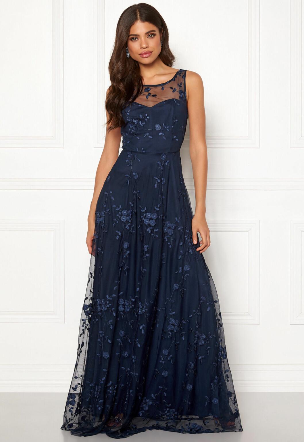 En bild på en mörkblå spetsklänning från Goddiva med rundad halsringning.