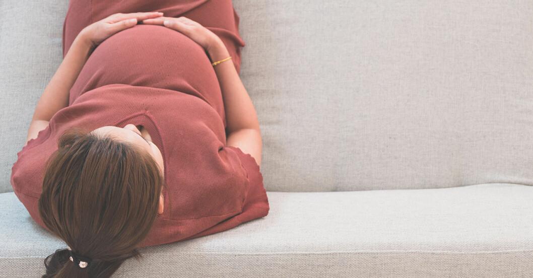 Gravid kvinna med tofs i soffa.