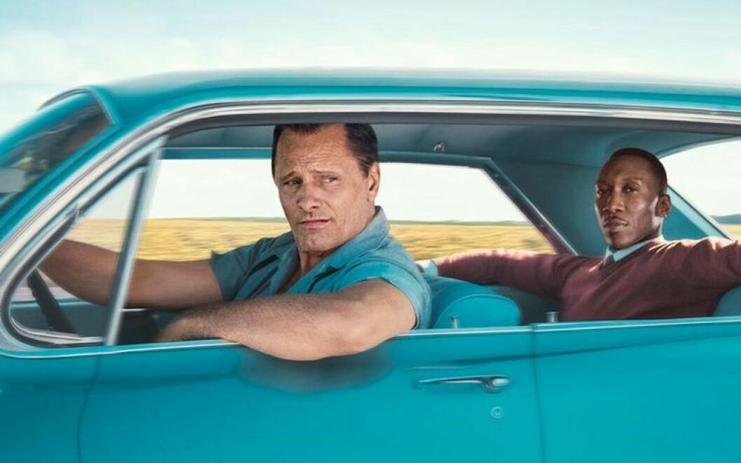 En man kör medan en annan sitter i baksätet i en blå bil.