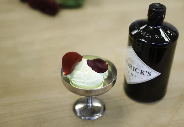 Glass med rosenblad och en flaska gin