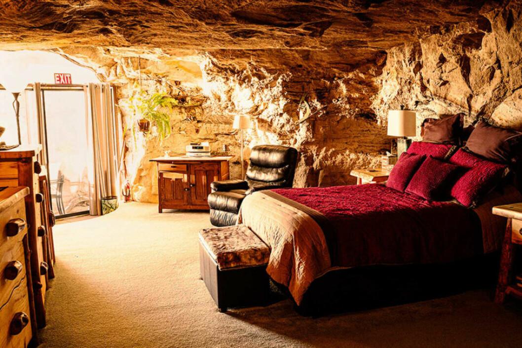 En säng med rött överkast i en grotta