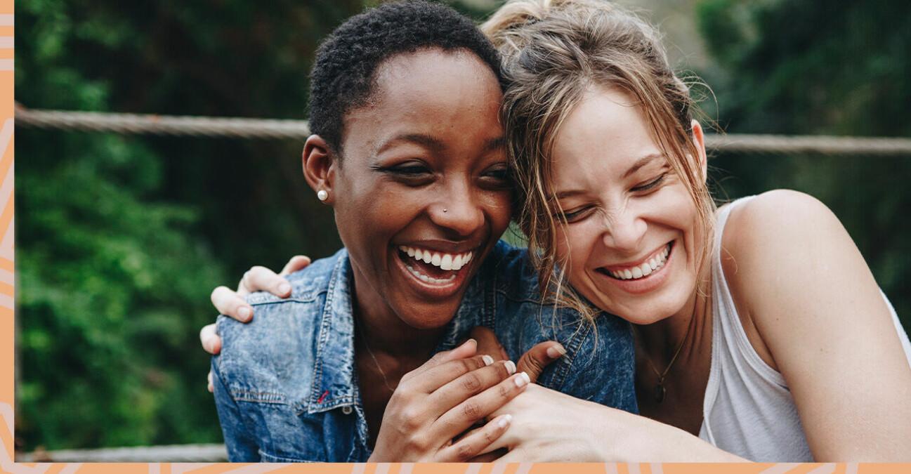 Två tjejer som skrattar och håller om varandra.