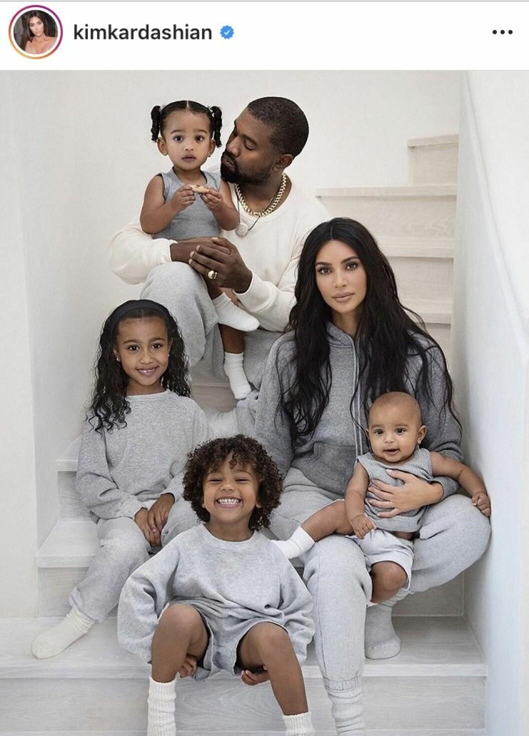 Kim Kardashian, Kanye West och deras barn sitter i en trapp iklädda grå mjukisar