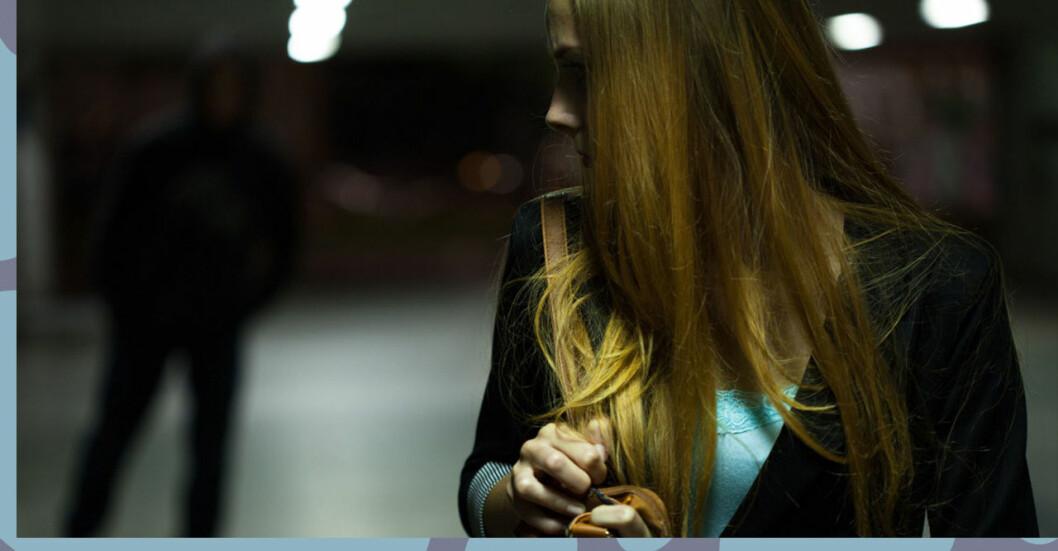 Kvinna går ensam hem på kvällen, man bakom. Många kvinnor känner sig otrygga när de går hem själva i mörkret.