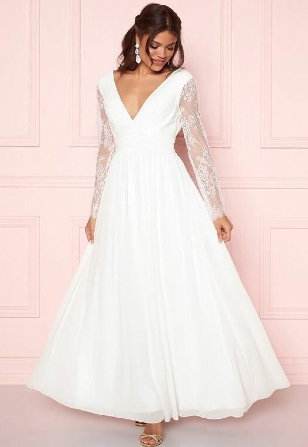 En bild på en långärmad brudklänning med djup v-ringning från Bubbleroom.