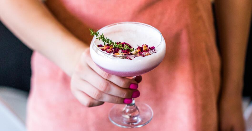 kvinna håller i lila drink med skum och blommor