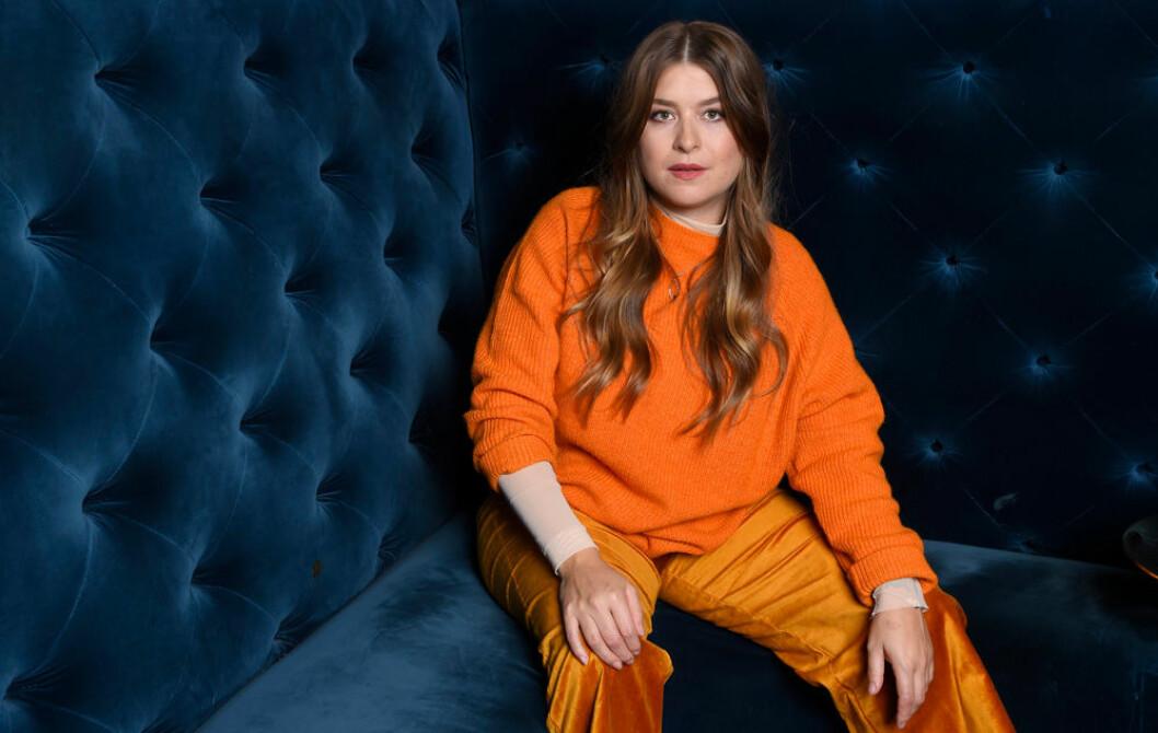 Linnea Henriksson i orange outfit när hon ger intervjuer för