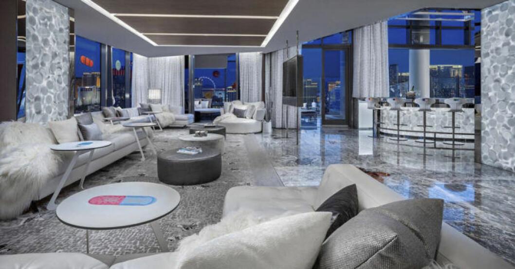 Stort vardagsrum inrett med marmor och konst.