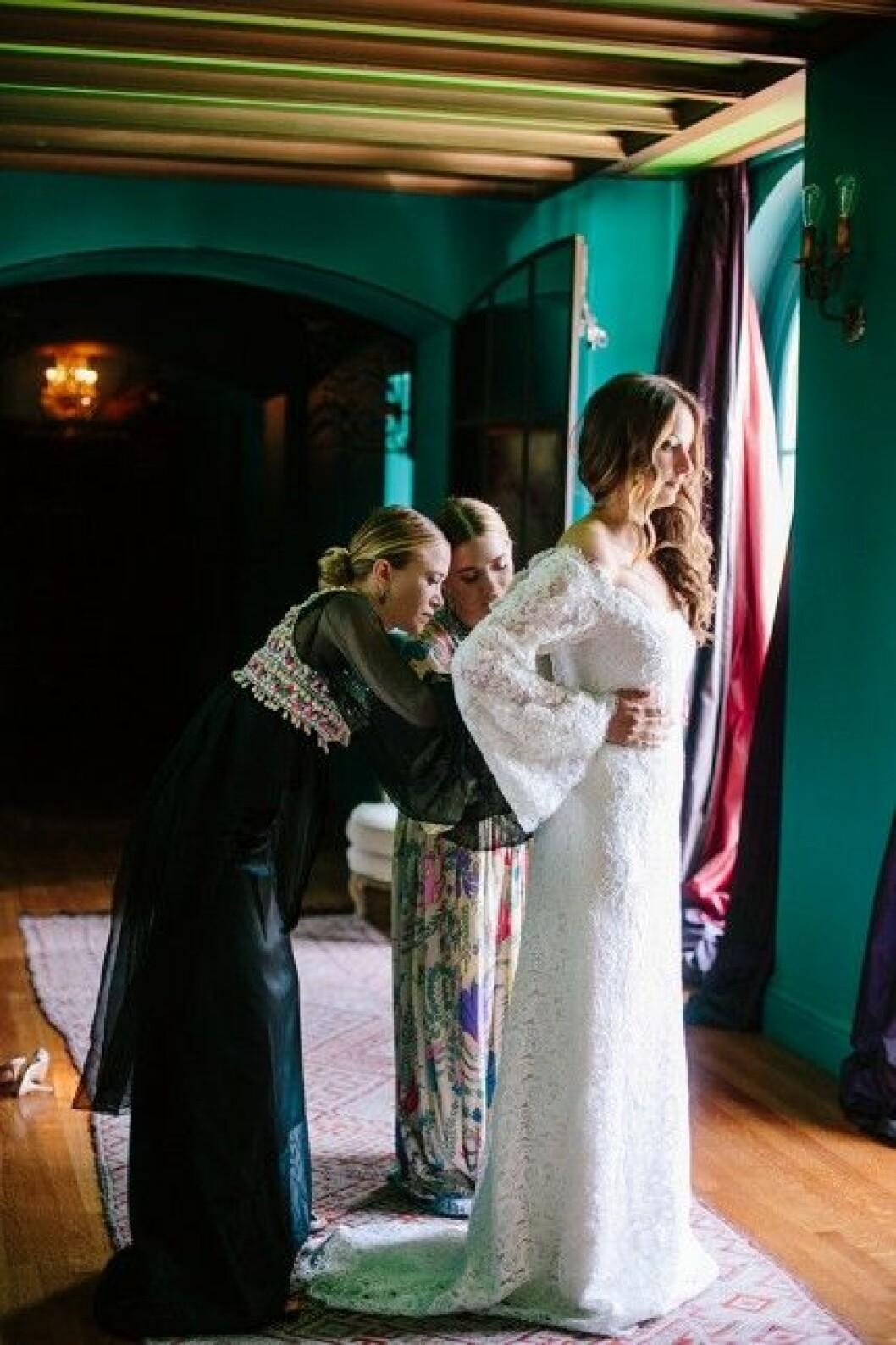 Mary-Kate och Ashley Olsen hjälper bruden Molly Fishkin med klänningen.