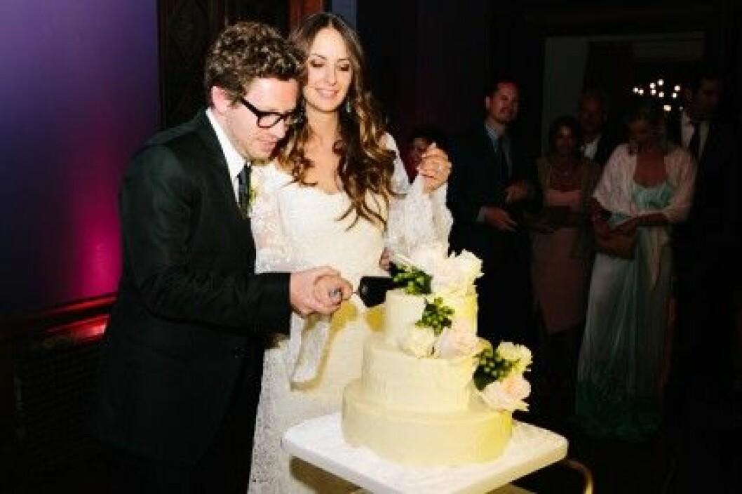 Bruden och brudgummen skär upp tårtan.