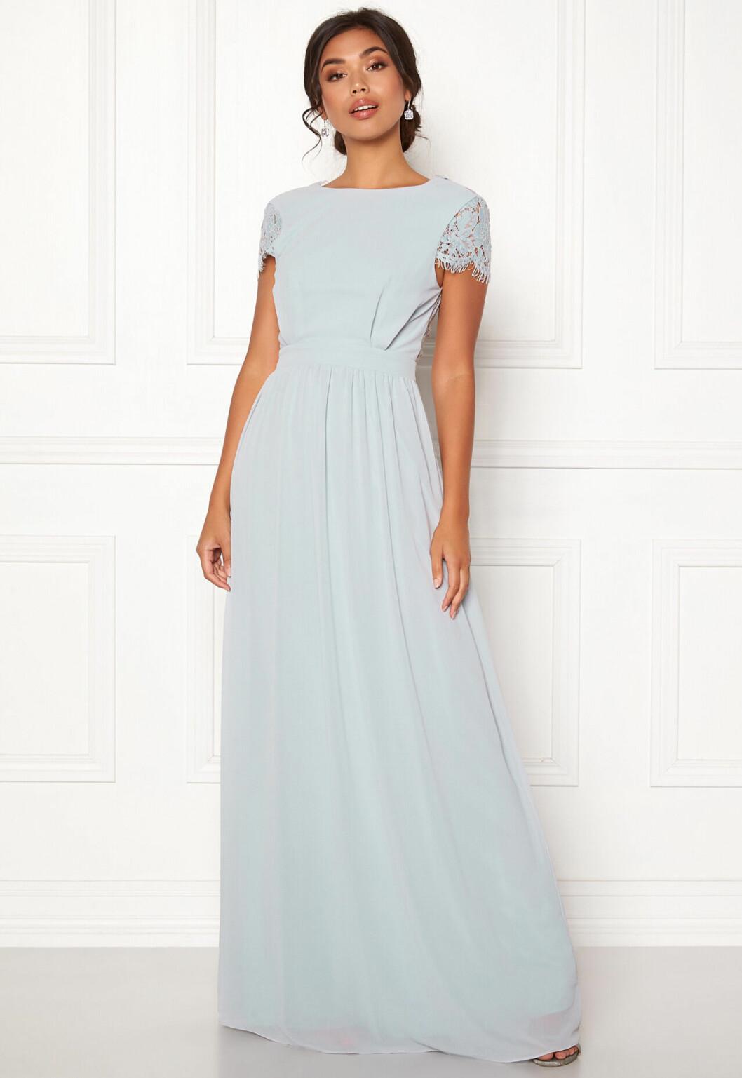 En bild på en ljusblå långklänning med spetsdetaljer från Moments New York.
