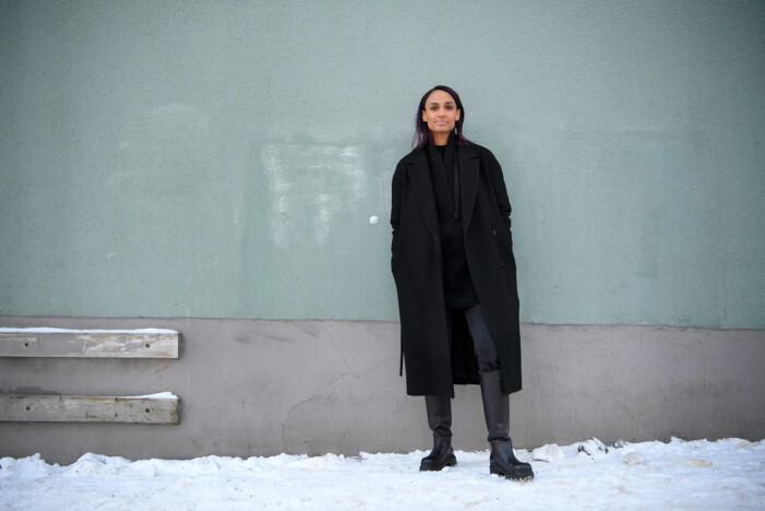 Nanna Blondell i svarta kläder mot grön vägg.