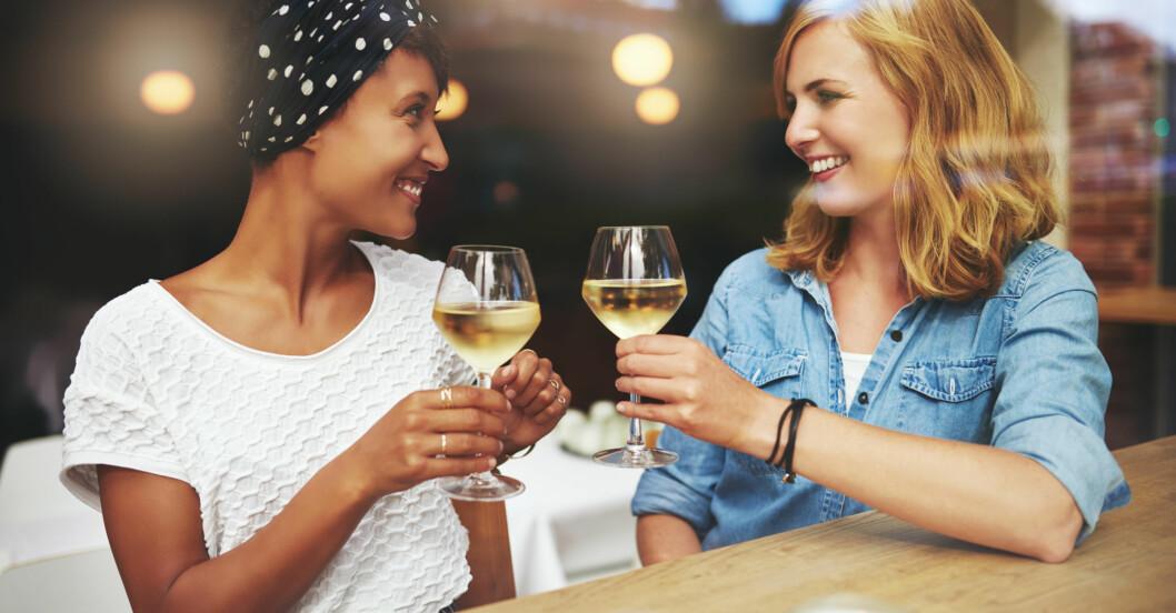 Tjejer skålar med vitt vin