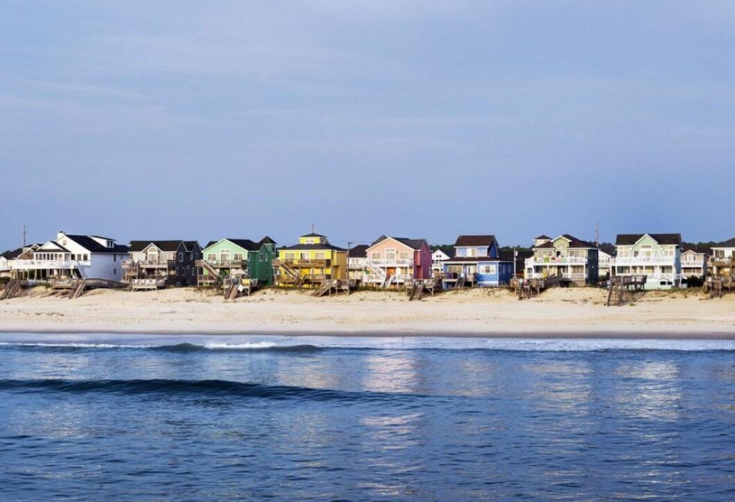 Färgglada strandhus precis vid vattnet och sanden