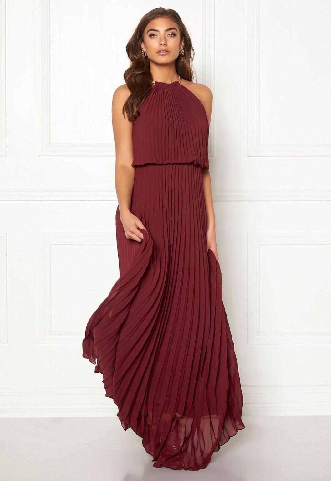 Röd långklänning i plisserat tyg till brudtärnan
