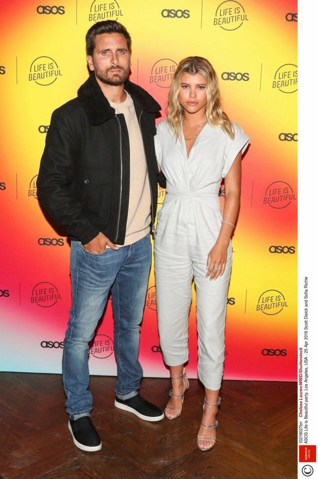 Scott Disick och Sofia Richie står bredvid varandra och håller om varandra