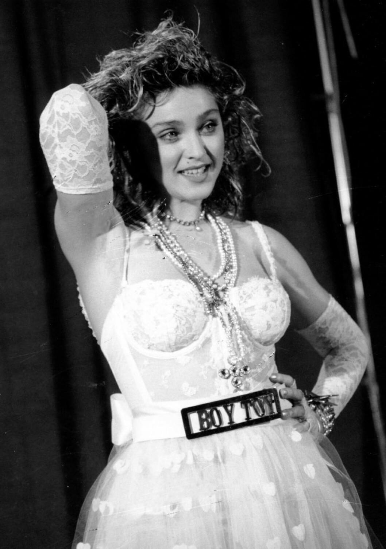 Madonna har en avslappnad hand i håret och ler.