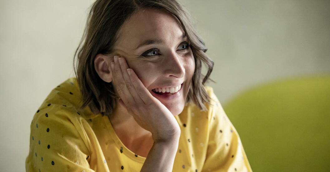 Josefin Asplund har en gul klänning och ler.