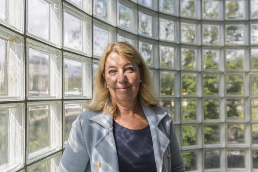 Annika Creutzer, ekonomijournalist och ekonomiexpert står framför en fönstervägg.-
