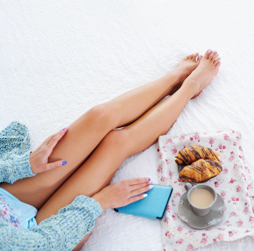 Woman beautiful legs in bed top view