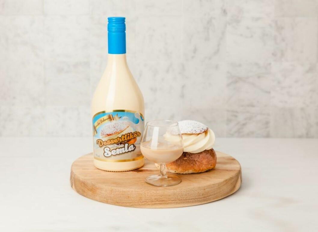 en semla, ett glas med likör och en flaska som står på en rund skärbräda i trä