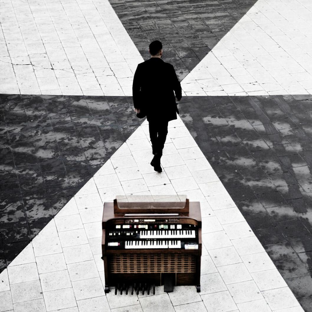 """Stor står på Sergels torg vid en flygel på omslaget till """"Stockholm står kvar men jag ligger"""" från Så mycket bättre. Ursprungligen en Eric Gadd-låt."""