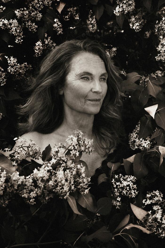 Suzanne Reuter naken bland blommor, svartvitt