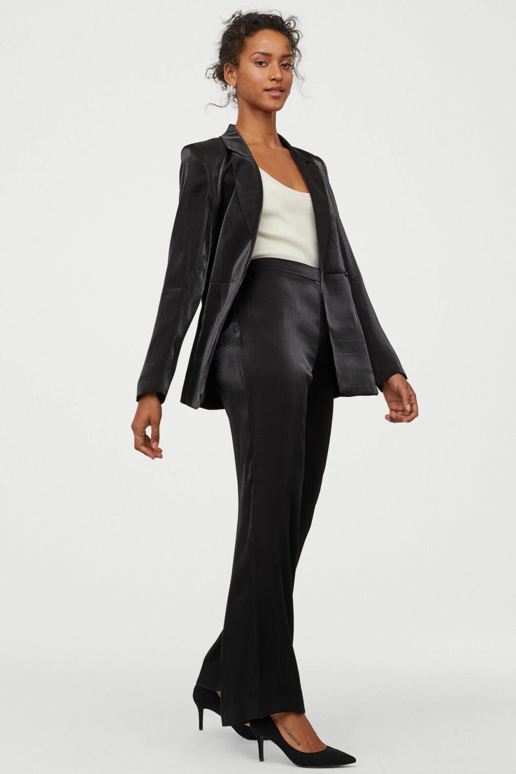 Svart kostym i glansigt material för dam
