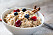 Oatmeal porridge with cinnamon, blueberries and cranberries in white bowl, close up selective focus image