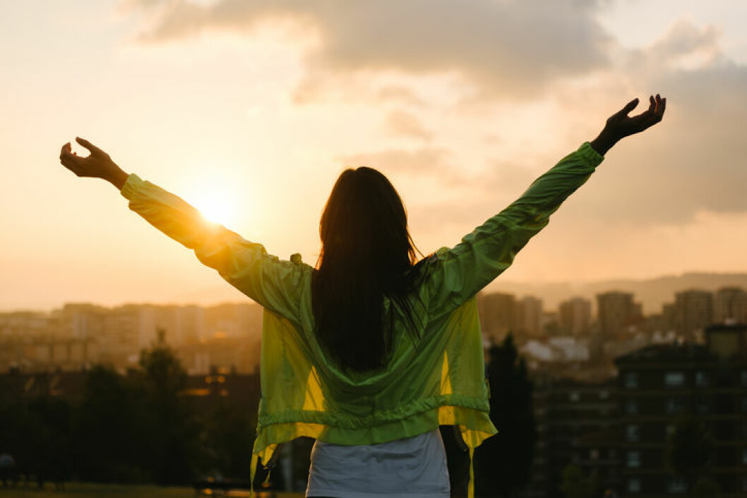 Back view of a blissful woman celebrating sport and fitness lifestyle success. Female athlete raising arms to the sky after exercising for relax towards beautiful sunset or morning over city skyline.