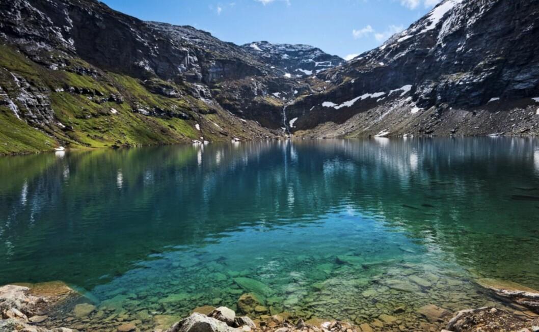turkos sjö med berg omkring